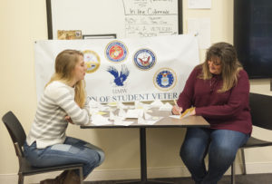 Student Michelle Justice, right, signs a thank-you card to a veteran as Jessica Roberson looks on.