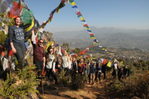 Those on the UMW trip to Nepal raise prayer flags above a sacred meditation cave in the foothills outside Kathmandu Valley. Photo by Dan Hirshberg.