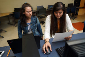 Natalie Florez (left) and Marlen Reyes (right), both UMW seniors, help tutor local teens at James Monroe High School in preparation for the GED test. Photo by Suzanne Rossi.