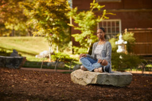 A student poses on a giant rock in UMW's Zen garden before COVID-19. Located between Trinkle and Mason halls, the garden is a peaceful outdoor spot for reflection and mindfulness. Photo by Adam Ewing.